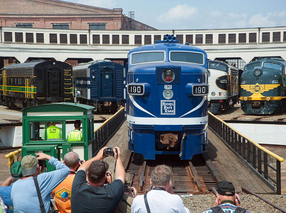 A group of rail fans taking photos of a vintage diesel locomotive